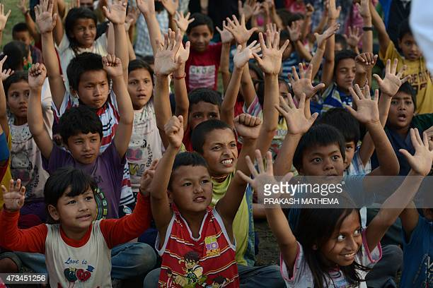 Nepalese children participate in a 'laughter yoga' session to help relieve trauma among survivors of two earthquakes which struck the country in less...