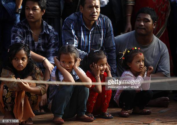 Nepalese children react as they watch a Nepalese soldier sacrificing a goat on the ninth day of the Hindu Dashain Festival in Kathmandu on October 10...