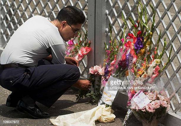 A Nepalese college student places flowers outside the gates of the royal palace in Kathmandu 03 June 2001 to pay his respects to the massacred...