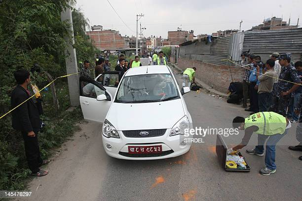 Nepalese crime officers examine the car in which a Supreme Court judge was shot in Kathmandu on May 31 2012 Gunmen on a motorbike shot and killed a...