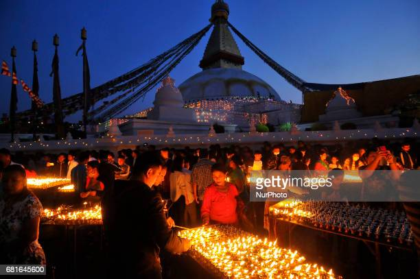 Nepalese devotee offering butter lamps at the premises of Boudhanath Stupa during celebration the 2,561 Buddha Purnima festival, Birth Anniversary of...