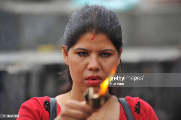 A Nepalese devotee offering butter lamps during Shrawan Sombar festival at the premises of Pashupatinath Temple Kathmandu Nepal on Monday July 24...