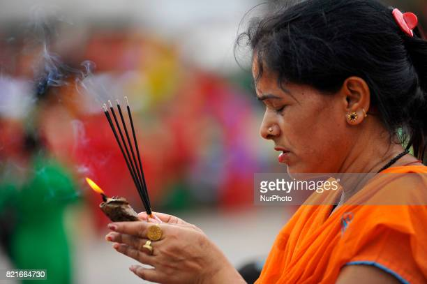 A Nepalese devotee offering incense fragrances during Shrawan Sombar festival at the premises of Pashupatinath Temple Kathmandu Nepal on Monday July...