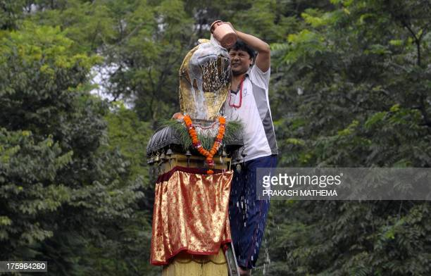 A Nepalese devotee pays obeisance by pouring cow's milk over a golden statue of the Hindu snake god known as 'Nag' at Nagpokhari in Kathmandu on...