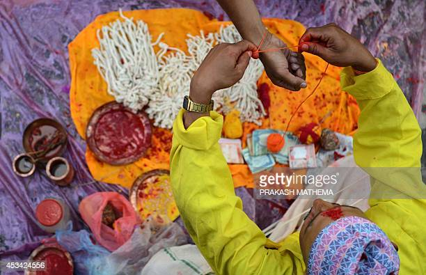 A Nepalese devotee receives a Janai or sacred thread which is a yellow cotton string worn across the chest or tied around the wrist of the right hand...