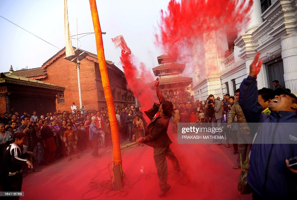 A Nepalese devotee throws coloured powder after devotees erected a ceremonial bamboo pole know as a 'Chir', fringed with strips of cloth and representing good luck charms, on the first day of Holi, the festival of colours at Basantapur Durbar Square in Kathmandu on March 20, 2013. The Holi festival is celebrated all over the country to mark the victory of God Rama over Rawan, the King of Evil and symbolises the arrival of the spring season. The final day of Holi festival falls on March 26, 2013. AFP PHOTO/Prakash MATHEMA