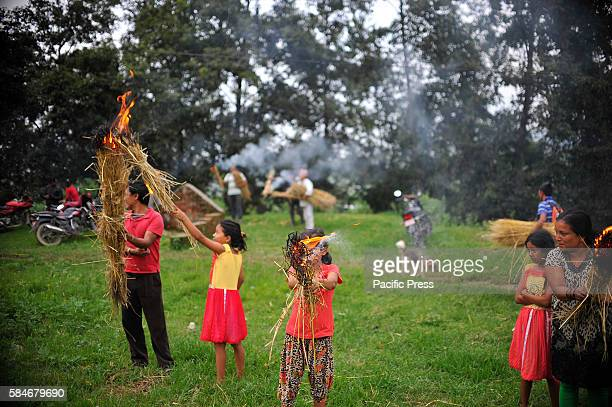 Nepalese devotees carry a traditional torch of straw as Priests carrying idol Rato Machindranath the small chariot towards the Bungamati after the...