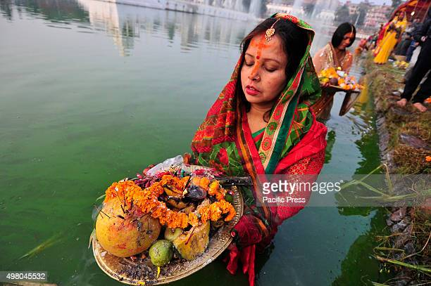 Nepalese devotees offer fruits to Sun God and wait for the rising sun on the 4th day of Chhath Puja Festival. Chhath Puja Festival, the worship of...