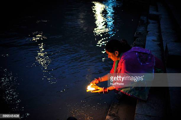 A Nepalese devotees offering oil and butter lamps at the Bank of Bagmati River of Pashupatinath Temple during Rishi Panchami Festival celebrations at...