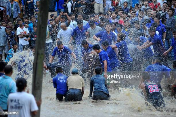 Nepalese devotees splash a water buffalo with water on Hanumante River as part of rituals before it is sacrificed on the ninth day of Dashain Hindu...