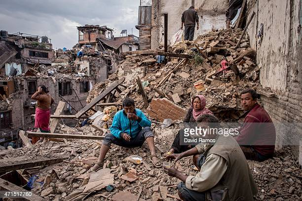 Nepalese earthquake victims take a break as they search for their belongings among debris of their home on April 29, 2015 in Bhaktapur, Nepal. A...