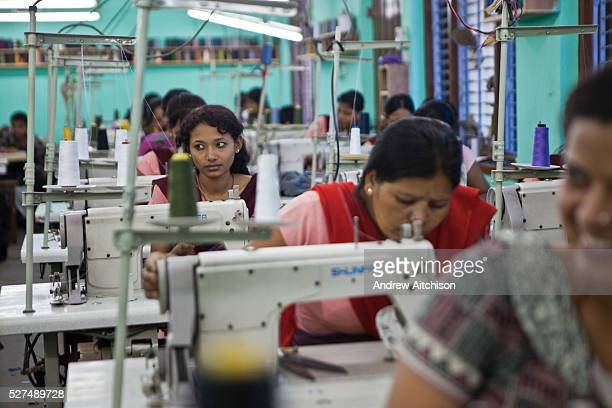 A Nepalese factory worker looks away from her work and listens to her colleagues talking at Surijha Traders garment factory in Kathmandu Nepal The...