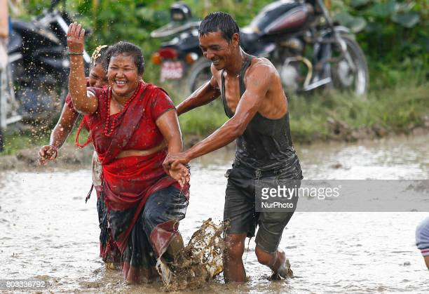 Nepalese farmer play with mud water during the celebration of Paddy Day also called 'Asar Pandra' festival to marks the commencement of rice crop...