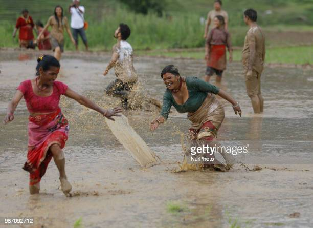Nepalese farmers throw mud water to each other at paddy field during National Paddy Day or Asar Pandra which marks the commencement of rice crop...