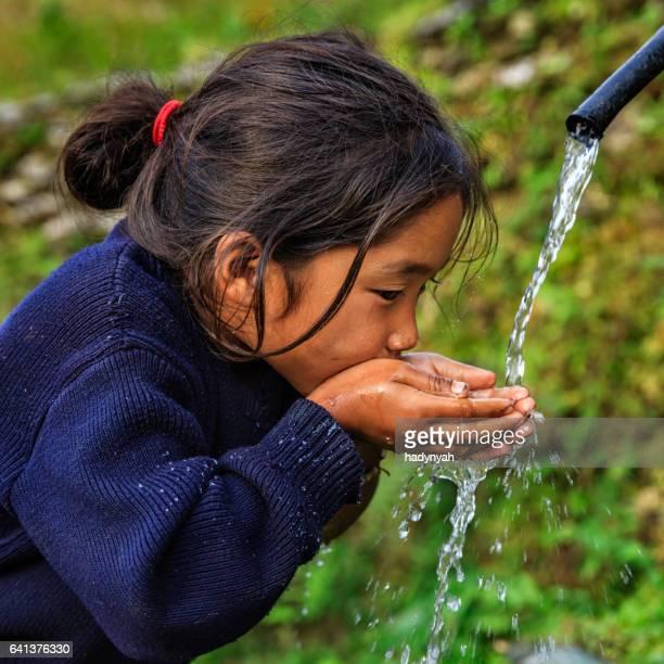 Nepalese girl drinking water, village near Annapurna Range