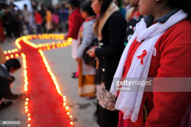A Nepalese girl put ribbon logo of RED AIDS during Eve of World AIDS Day celebrated in Kathmandu Nepal on 1st Dec 2017 World AIDS Day is celebrated...