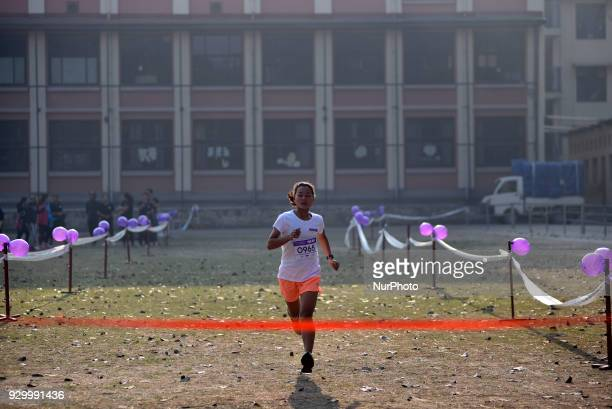 A Nepalese girl running on an International Women's Day 5K Fun Run at Patan Nepal on Saturday March 10 2018 Nepalese people and foreigners Celebrate...