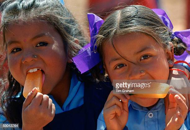 Nepalese girls enjoying orange ice lollies in rural Nepal
