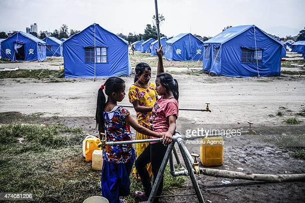 Nepalese girls wait to fill their buckets with fresh water at the earthquake survivors temporarily shelter in Kathmandu, Nepal on May 20 following...