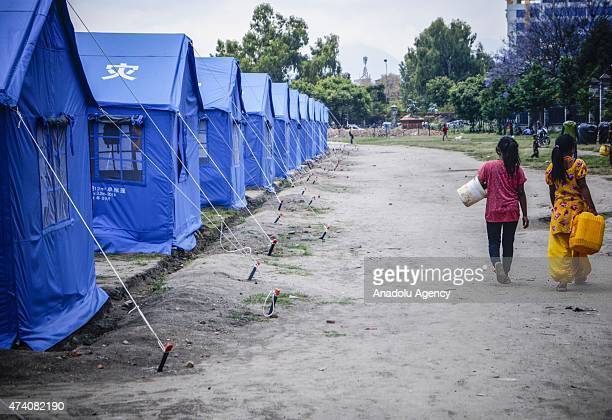 Nepalese girls walk with empty buckets to fill them with fresh water at the earthquake survivors temporarily shelter in Kathmandu, Nepal on May 20...