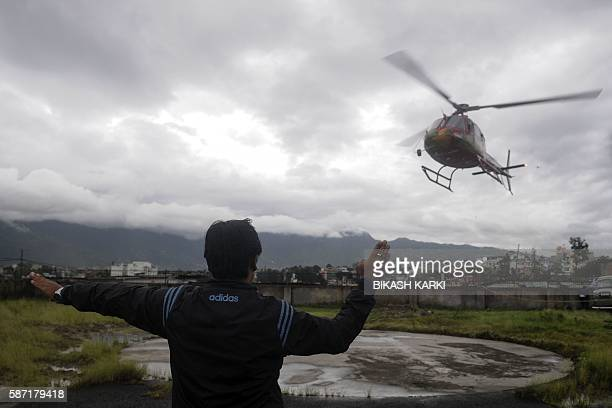 A Nepalese groundstaff personnel for the Fishtail Helicopter company directs a helicopter as it arrives at the morgue of the Teaching Hospital in...