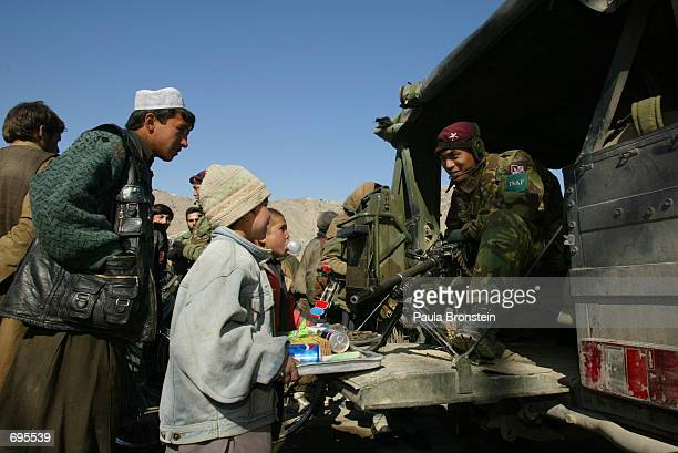 Nepalese Gurkha from the British regiment of the Bruneval Company on patrol through the city of Kabul speak with local Afghans February 9 2002 in...