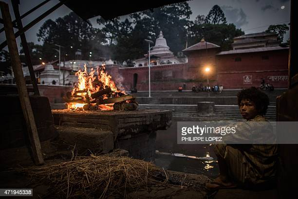 A Nepalese Hindu boy sits near a funeral pyre as a body is cremated in Kathmandu on May 2 2015 AFP PHOTO / PHILIPPE LOPEZ