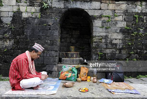 A Nepalese Hindu Brahmin priest waits for devotees during the Rishi Panchami festival in Kathmandu on September 6 2016 Rishi Panchami marks the end...