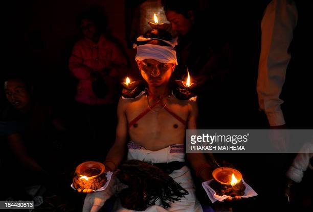 Nepalese Hindu devotee holds burning oil lamps on his head and palms for six hours on the tenth day of Hindu's biggest festival, Dashain , in...