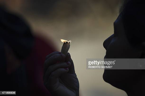 A Nepalese Hindu devotee holds up lit wicks as she offers a prayer in front of a statue of Hindu diety Kaal Bhairab in the Durbar Square...