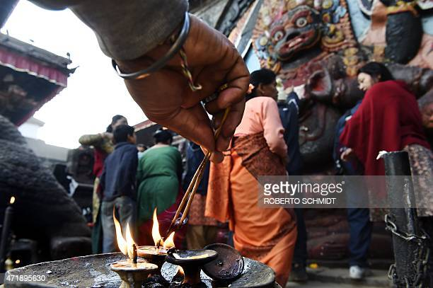 A Nepalese Hindu devotee lights incense sticks as others like him gather in front of a statue of Hindu diety Kaal Bhairab in the Durbar Square...