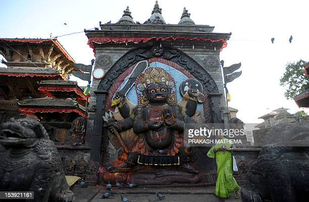 A Nepalese Hindu devotee walks past the Kaal Bhairav idol in Durbar square in Kathmandu on October 11 2012 The Durbar Square holds the palaces of the...