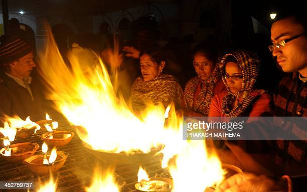 Nepalese Hindu devotees hold light oil lamps in memory of deceased family members during the Balachaturdashi festival at the Pashupatinath temple in...