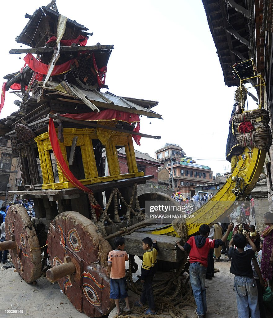 Nepalese Hindu devotees stand near a wooden chariot during the second day of Bisket Jatra, a festival in Bhaktapur, some 12 kms east of Kathmandu on April 11, 2013. Two people died in Nepal after being crushed under the wheels of a 10-metre-high (35-foot) wooden chariot being used during a new year festival that descended into chaos, police said. AFP PHOTO/ Prakash MATHEMA