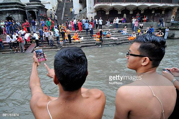 Nepalese Hindu devotees takes selfie after taking holy bath during Janai Purnima festival or Rakchhya Bandhan at Pashupatinath Temple Kathmandu Nepal...