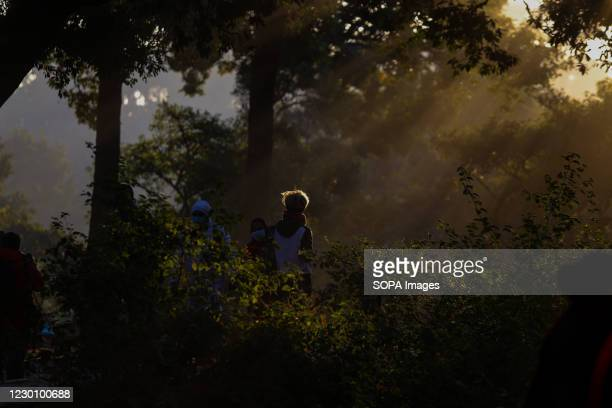 Nepalese Hindu devotees walk at the premises of Pashupatinath temple early morning scattering seeds in memory of deceased family members during Bala...