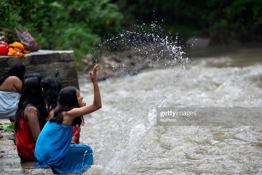 Nepalese Hindu girl playing in water before takes a ritual bath at the Bagmati River of Pashupatinath Temple during Rishi Panchami Festival celebrations at Pashupatinath Temple, Katmandu, Nepal on Friday, September 14, 2018. Rishi Panchami festival is celebrated as the last day of three-day long Teej Festival. The Teej festival is celebrated by Hindu women in Nepal as well as in some parts of India. During the three-day long festival, women observe a day-long fast and pray for the long life their husbands as well as for a happy family. Those who are unmarried pray for a good husband and a long life.