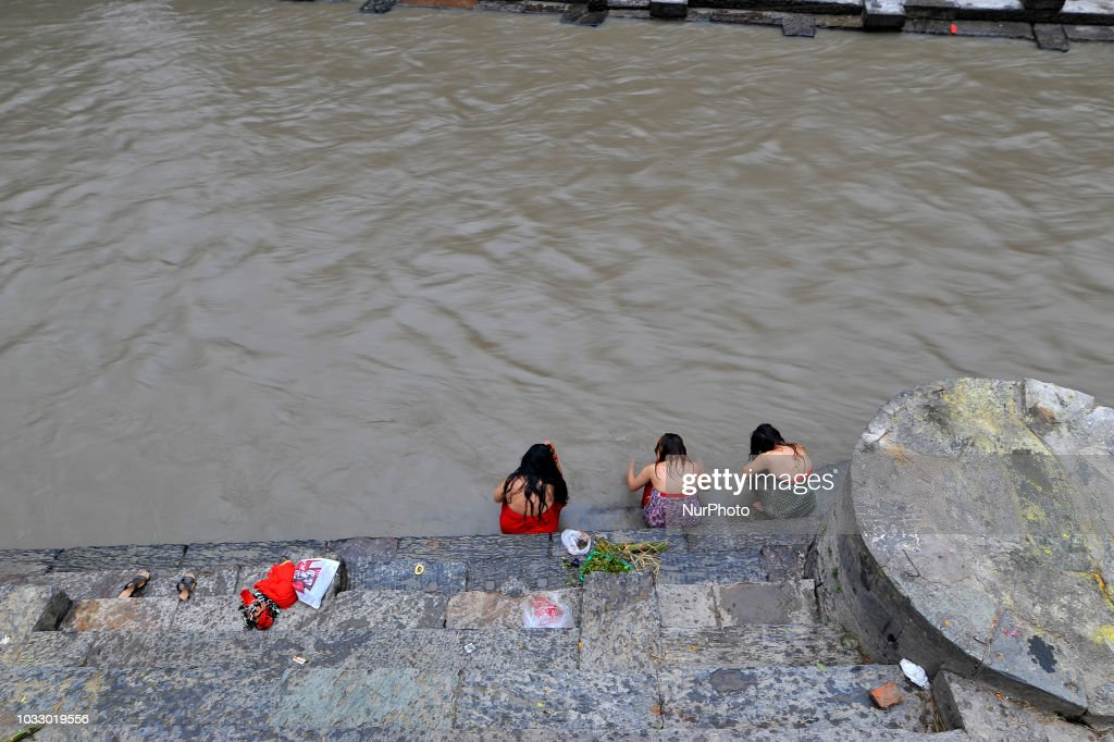 Nepalese Hindu girls performing rituals at the Bagmati River of Pashupatinath Temple during Rishi Panchami Festival celebrations at Pashupatinath Temple, Katmandu, Nepal on Friday, September 14, 2018. Rishi Panchami festival is celebrated as the last day of three-day long Teej Festival. The Teej festival is celebrated by Hindu women in Nepal as well as in some parts of India. During the three-day long festival, women observe a day-long fast and pray for the long life their husbands as well as for a happy family. Those who are unmarried pray for a good husband and a long life.