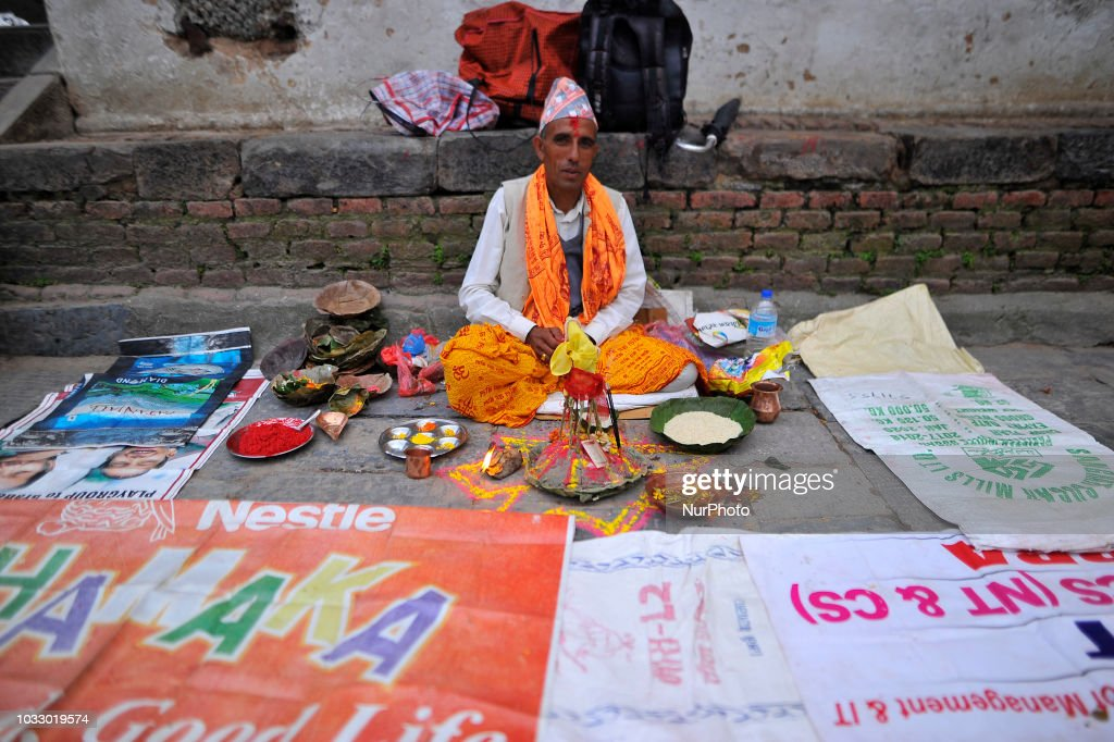 A Nepalese Hindu priest waits for devotees to offer rituals at the Bagmati River of Pashupatinath Temple during Rishi Panchami Festival celebrations at Pashupatinath Temple, Katmandu, Nepal on Friday, September 14, 2018. Rishi Panchami festival is celebrated as the last day of three-day long Teej Festival. The Teej festival is celebrated by Hindu women in Nepal as well as in some parts of India. During the three-day long festival, women observe a day-long fast and pray for the long life their husbands as well as for a happy family. Those who are unmarried pray for a good husband and a long life.