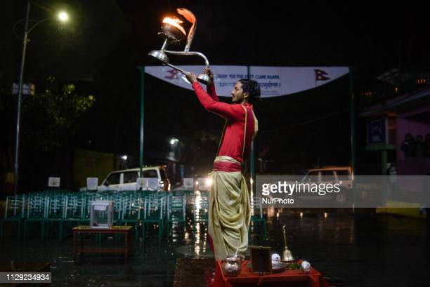 Nepalese Hindu priests perform evening Aarti ceremony during heavy rain at the Phewa Lake Pokhara Nepal on March 8 2019