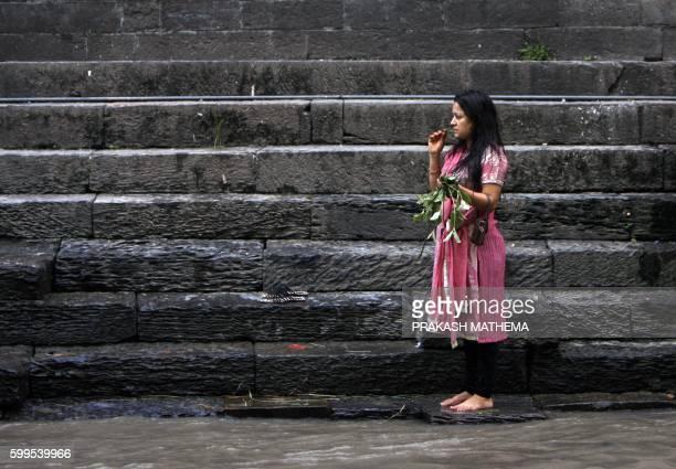 Nepalese Hindu woman brushes her teeth before taking a ritual bath in the Bagmati river during the Rishi Panchami festival in Kathmandu on September...
