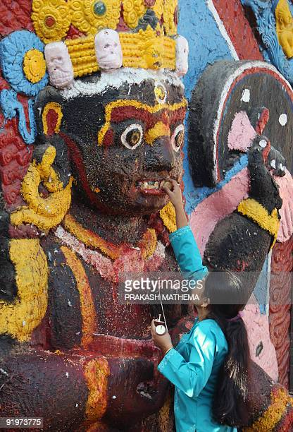 A Nepalese Hindu woman offers prayers in front of a statue of Hindu God of Destruction Kaal Bhairab at Durbar Square in Kathmandu on October 18 2009...