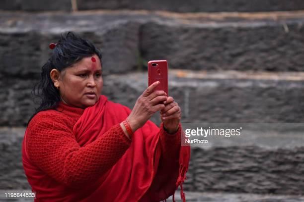 Nepalese Hindu woman takes pictures from mobile during Madhav Narayan Festival or Swasthani Brata Katha at Pashupathnath Temple, Kathmandu, Nepal on...