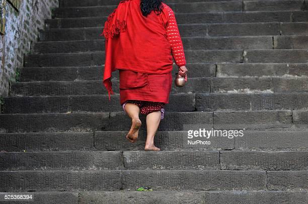 A Nepalese Hindu woman walk on a stairs to offer ritual prayer at Shes Narayan Temple Pharping Kathmandu during Madhav Narayan Festival on 9 February...