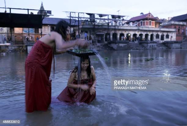 Nepalese Hindu women take a ritual bath in the Bagmati river during 'Rishi Panchami' in Kathmandu early on September 18 2015 Rishi Panchami marks the...