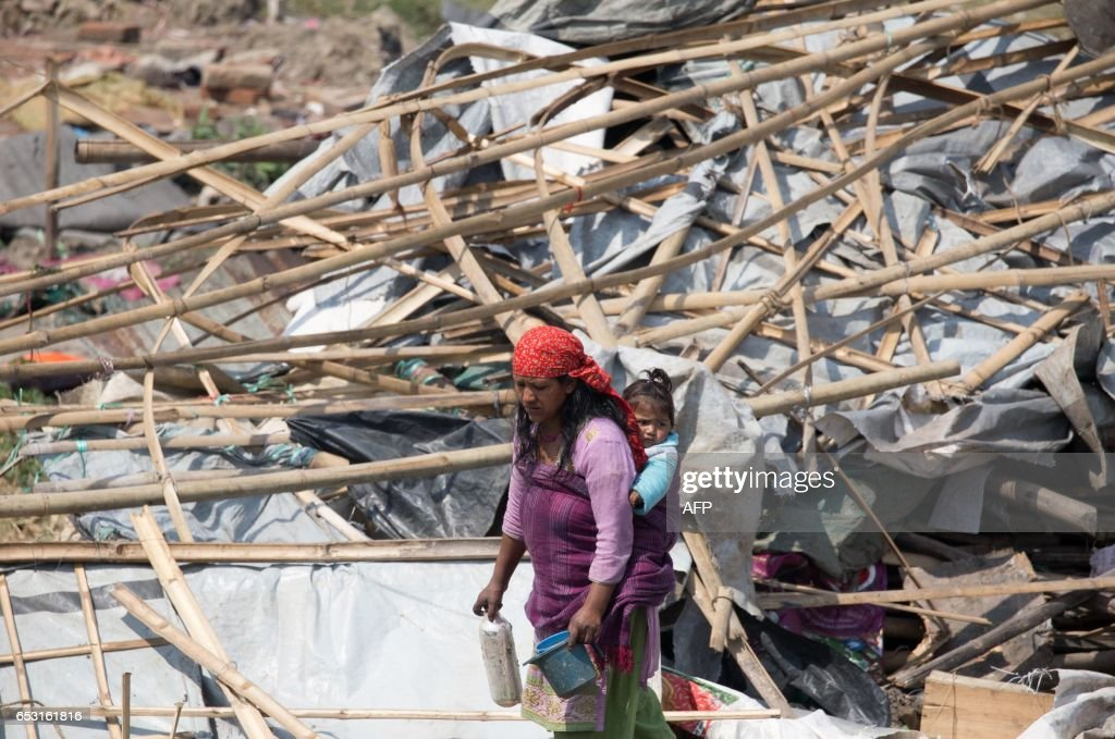 A Nepalese homeless woman walks through the remains of a makeshift camp for people displaced by the 2015 earthquake after it was demolished by police in Kathmandu on March 14, 2017. Nepal police on March 14 demolished the largest remaining settlement of people displaced by a powerful earthquake that struck nearly two years ago, a move that will leave hundreds homeless. Around 100 families were still living in the camp in Kathmandu when police wearing riot gear used bulldozers to flatten the bamboo and tarpaulin structures. / AFP PHOTO / Sulav SHRESTHA