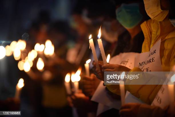 Nepalese Human Rights activists hold candle lights along with placard during protest against the Myanmar military coup in front of Boudhanath Stupa,...