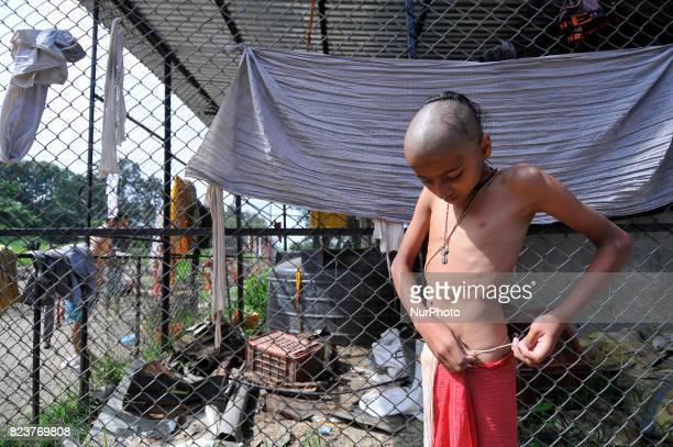 A Nepalese kid from Hindu school Bhagwat Sanyaas Aashram Gurukul changing cloth after taking rituals holy bath during Janai Purnima festival or...