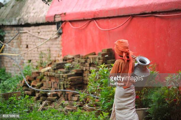 A Nepalese kid from Hindu school Bhagwat Sanyaas Aashram Gurukul carrying holy water for rituals offering during Nag Panchami festival at...