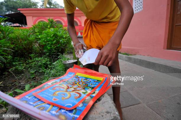 A Nepalese kid from Hindu school Bhagwat Sanyaas Aashram Gurukul prepare to stics a picture of a snake god at the main entrance during Nag Panchami...